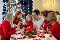 Familj med ungar som har julmatställen på trädet arkivbild
