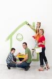 Familj med ungar som målar deras hem royaltyfri fotografi
