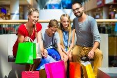 Familj med ungar som shoppar i galleria Royaltyfria Bilder