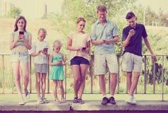 Familj med ungar som spelar med mobiltelefoner Arkivfoto