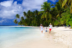Familj med ungen som spelar på stranden Royaltyfria Bilder
