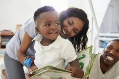 Familj med ungt barnläseboken i lekrum tillsammans arkivbild