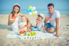Familj med vattenmelon på stranden Arkivfoton