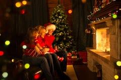 Familj - moder, fader och unge som ser spisen i jul dekorerad husinre Arkivfoto