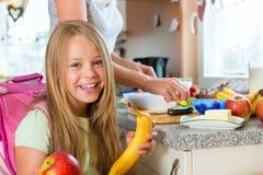 Familj - moder som gör frukosten för skola Arkivfoton