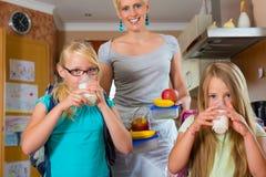 Familj - moder som gör frukosten för skola Royaltyfria Bilder