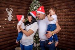 Familj nära jultreen Föräldrar med barn på trädet Nytt år magisk tid arkivfoto