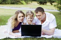 Familj och bärbar dator royaltyfri foto