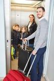 Familj och barn i flygplatselevatorn på stopoveren royaltyfri bild