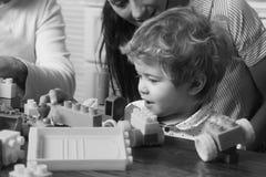 Familj och barndombegrepp Behandla som ett barn pojkeblickar på drevet som göras ut ur konstruktionskvarter Arkivfoton