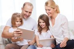 Familj och två ungar med minnestavlaPCdatorer Royaltyfri Bild