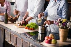 Familj och vänner som lagar mat mat på matställetabellen royaltyfri bild