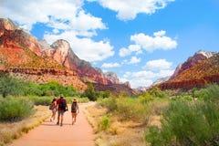 Familj på att fotvandra tur i bergen som går på bana Royaltyfri Bild
