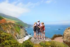Familj på att fotvandra tur som tycker om härliga sommarberg, kust- landskap, Arkivfoto