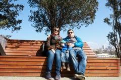 Familj på bänk i vår arkivfoto