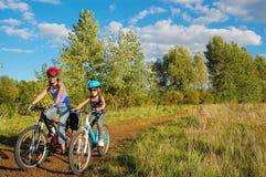 Familj på cyklar utomhus, aktiv moder och unge som cyklar, kondition och sund livsstil royaltyfria foton