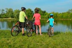 Familj på cyklar utomhus, aktivföräldrar och ungen som cyklar och kopplar av nära den härliga floden, kondition royaltyfri bild