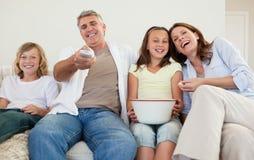 Familj på den hållande ögonen på tv:n för sofa Royaltyfri Bild