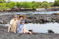 Familj på den svart sandstranden Arkivbild