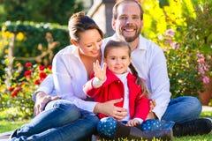 Familj på den trädgårds- gräsmattan Arkivfoto