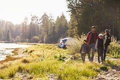 Familj på en campa tur som går nära en sjö arkivbilder