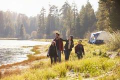 Familj på en campa tur som går nära en sjö som bort ser arkivbilder