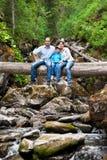 Familj på en fallen tree över floden Fotografering för Bildbyråer