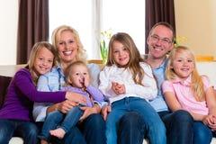 Familj på en soffa royaltyfria bilder