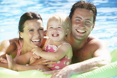Familj på ferie i simbassäng royaltyfria bilder