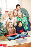 Familj på jul som rymmer tummar Royaltyfri Foto