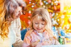 Familj på juldagen som packar upp gåvor under trädet fotografering för bildbyråer