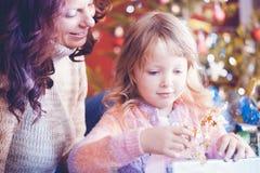 Familj på juldagen som packar upp gåvor under trädet royaltyfria bilder