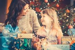 Familj på juldagen som packar upp gåvor under trädet royaltyfri fotografi