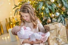 Familj på julhelgdagsafton på spisen Ungar som öppnar Xmas-gåvor Barn under julgranen med gåvaaskar Dekorerad uppehälle royaltyfria foton
