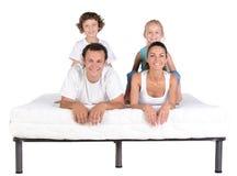 Familj på madrassen Fotografering för Bildbyråer