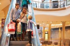 Familj på rulltrappan i shoppinggalleria tillsammans Arkivbilder