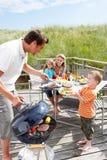 Familj på semestern som har grillfesten Arkivbilder