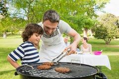 Familj på semestern som har grillfesten Arkivbild