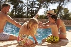 Familj på semestern som har gyckel vid den utomhus- pölen royaltyfria bilder