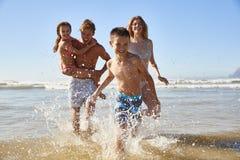 Familj på sommarstrandsemestern som körs ut ur havet in mot kamera arkivbild