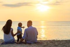 Familj på strandbegreppet, Caucasian pojke som placerar och rymmer sa arkivfoton