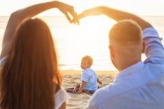 Familj på strandbegreppet, Caucasian pojke som placerar och rymmer sa arkivfoto