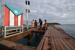 Familj på stranden bredvid flagga i Vieques, Puerto Rico Arkivfoton