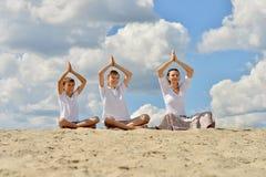 familj på stranden som gör yoga royaltyfri foto