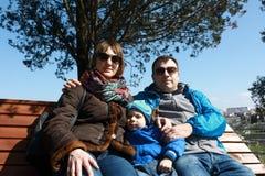 Familj på träbänk i vår royaltyfria bilder