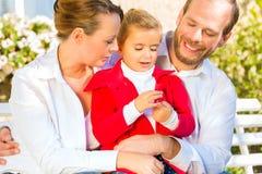 Familj på trädgårds- bänk framme av hemmet Royaltyfria Foton