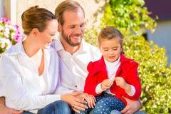 Familj på trädgårds- bänk framme av hemmet Arkivfoton