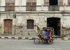 Familj på trehjulingritt i stad av Vigan arkivfoton