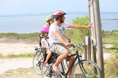 Familj på att cykla resan vid havet Arkivbild