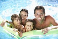 Familj på ferie i simbassäng Royaltyfri Bild